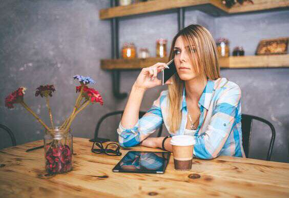 worried young woman talking on smartphone in cafe